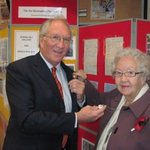 In front of 3rd Pals exhibition John Bradshaw and Jean Perks examining mementos they wear of their ancestors WW1 servi